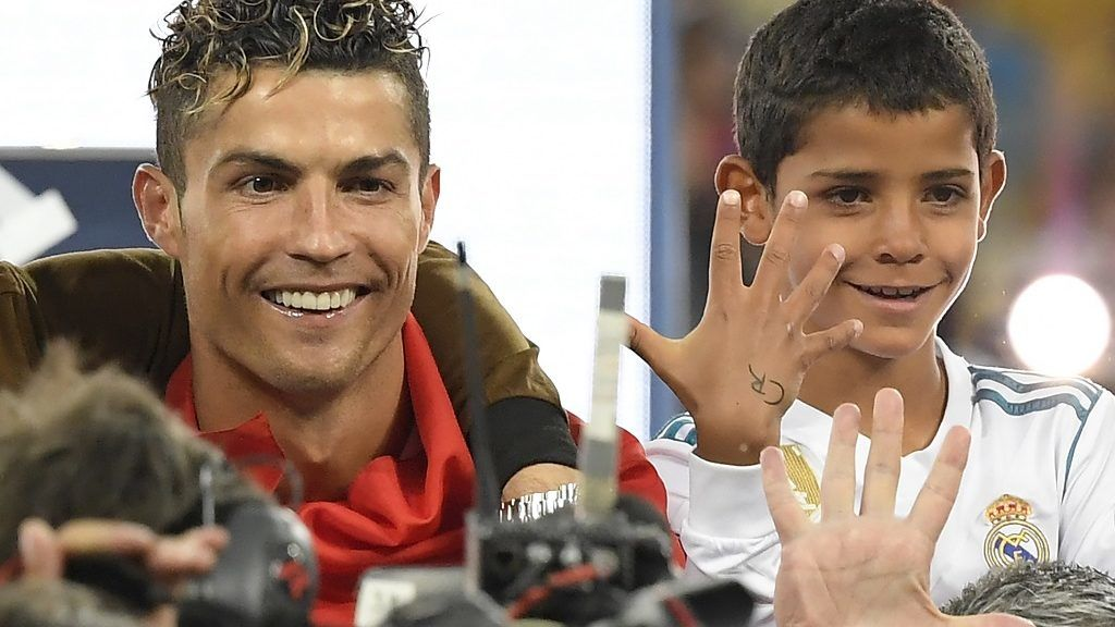 Real Madrid's Portuguese forward Cristiano Ronaldo celebrates with his son Cristiano junior after winning the UEFA Champions League final football match between Liverpool and Real Madrid at the Olympic Stadium in Kiev, Ukraine on May 26, 2018. Real Madrid defeated Liverpool 3-1. / AFP PHOTO / LLUIS GENE