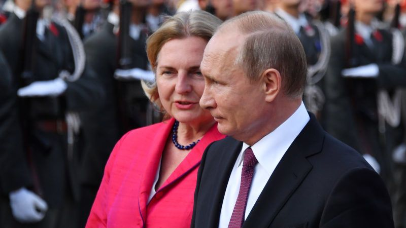 Russian President Vladimir Putin (R) and Austrian Foreign Minister Karin Kneissl take part in a wreath laying cermony at the Soviet World War II memorial in Vienna, Austria, June 5, 2018.  President Putin is on a one-day state visit to Austria. / AFP PHOTO / JOE KLAMAR