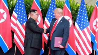 """In this picture taken on June 12, 2018 and released from North Korea's official Korean Central News Agency (KCNA) on June 13, 2018, US President Donald Trump (R) and North Korea's leader Kim Jong Un (L) shake hands after signing documents at a signing ceremony during their historic US-North Korea summit, at the Capella Hotel on Sentosa island in Singapore. / AFP PHOTO / KCNA VIA KNS / - / South Korea OUT / REPUBLIC OF KOREA OUT ---EDITORS NOTE--- RESTRICTED TO EDITORIAL USE - MANDATORY CREDIT """"AFP PHOTO/KCNA VIA KNS"""" - NO MARKETING NO ADVERTISING CAMPAIGNS - DISTRIBUTED AS A SERVICE TO CLIENTS / THIS PICTURE WAS MADE AVAILABLE BY A THIRD PARTY. AFP CAN NOT INDEPENDENTLY VERIFY THE AUTHENTICITY, LOCATION, DATE AND CONTENT OF THIS IMAGE. /"""