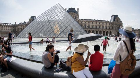 Tourists cool themselves at the fountain in front of the Louvre Pyramid in Paris on August 7, 2018, during an on-going heatwave in Europe.   / AFP PHOTO / GERARD JULIEN
