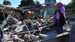 A woman and boy watch as men clear the wreckage of houses damaged by an earthquake in Menggala, North Lombok on August 8, 2018, three days after the earthquake struck the area. The shallow 6.9-magnitude quake destroyed thousands of buildings and triggered panic among tourists and locals on Lombok on August 5, just a week after a tremor had surged through the holiday island and killed 17. / AFP PHOTO / ADEK BERRY