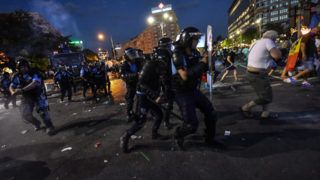 """Romanian anti riot police clash with protesters during a demonstration in front of the Romanian Government headquarters in Bucharest August 10, 2018, to protest against the government.  Romanian police used tear gas and pepper spray to quell anti-corruption protesters in Bucharest on August 10, 2018, as tens of thousands called on the leftwing government to resign. Local media said between 30,000 to 50,000 people turned out for the protest, included many Romanian expatriates who returned home especially to show their anger at the levels of official corruption.  The crowd chanted """"resign"""" and """"thieves"""" as they assembled in a central square outside the main government building.  / AFP PHOTO / Daniel MIHAILESCU"""