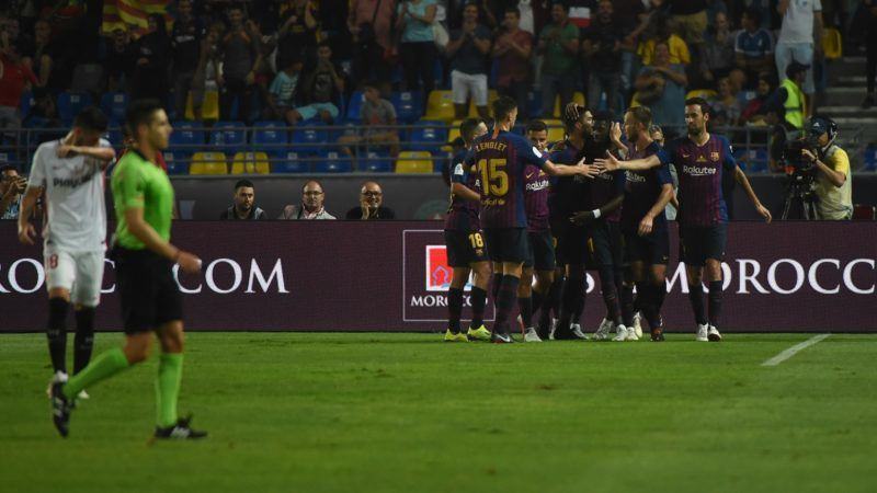 Barcelona's players celebrate with Barcelona's French forward Ousmane Dembele after his goal during the Spanish Super Cup final between Sevilla FC and FC Barcelona at Ibn Batouta Stadium in the Moroccan city of Tangiers on August 12, 2018. / AFP PHOTO / FADEL SENNA