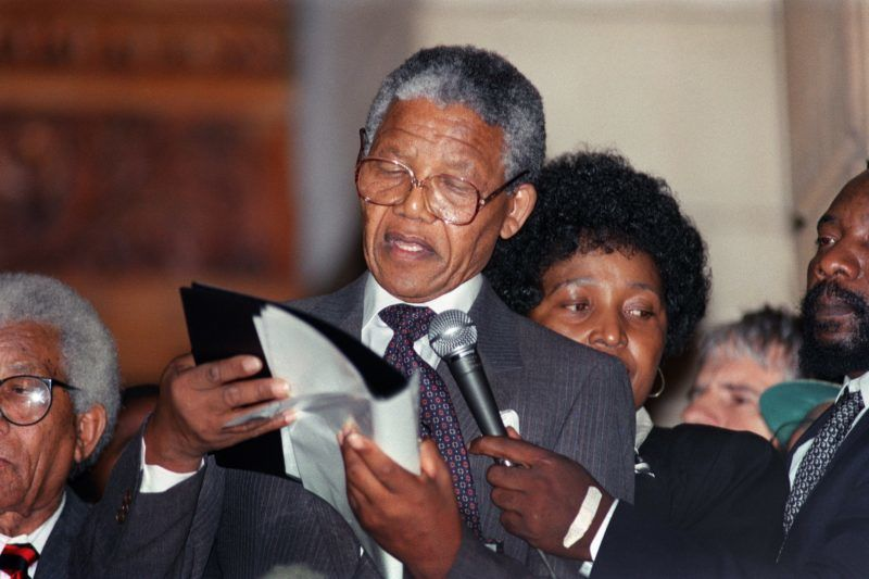Anti-apartheid leader and African National Congress (ANC) member Nelson Mandela delivers his first public speech in Cape Town, 11 February 1990, since his release from jail. He urged white South Africans to join ANC in working for a new South Africa. At right, Mandela's wife Anti-apartheid campaigner Winnie Mandela . / AFP PHOTO / Walter DHALDHLA