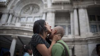 Activists and members of the Lesbian, Gay, Bisexual, Transgender, Transvestite, Transgender and Intersex (LGBTTTI) communities kiss during an activity for the International Day against Homophobia in front of the Palace of Fine Arts in Mexico City on May 17, 2016.  / AFP PHOTO / YURI CORTEZ