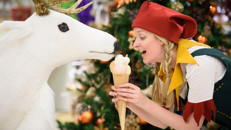 A Christmas elf poses with an ice cream and a toy reindeer during a promotional event to launch the Selfridges Christmas Shop in their flagship store in central London on August 3, 2015. With 142 shopping days until Christmas, Selfridges is the first store to open it's festive department this year. AFP PHOTO/Leon Neal / AFP PHOTO / LEON NEAL