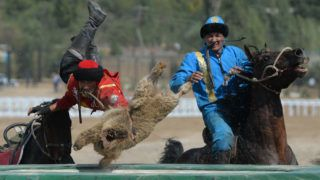 Kazakh and Kyrgyz (red) riders play the traditional Central Asian sport Buzkashi also known as Kok-Boru or Oglak Tartis during the World Nomad Games 2016 in Cholpon-Ata on the shores of Lake Issyk-Kul, some 270 kms outside the capital Bishkek, on September 8, 2016.   Mounted players compete for points by throwing a stuffed sheepskin into a well. / AFP PHOTO / Vyacheslav OSELEDKO