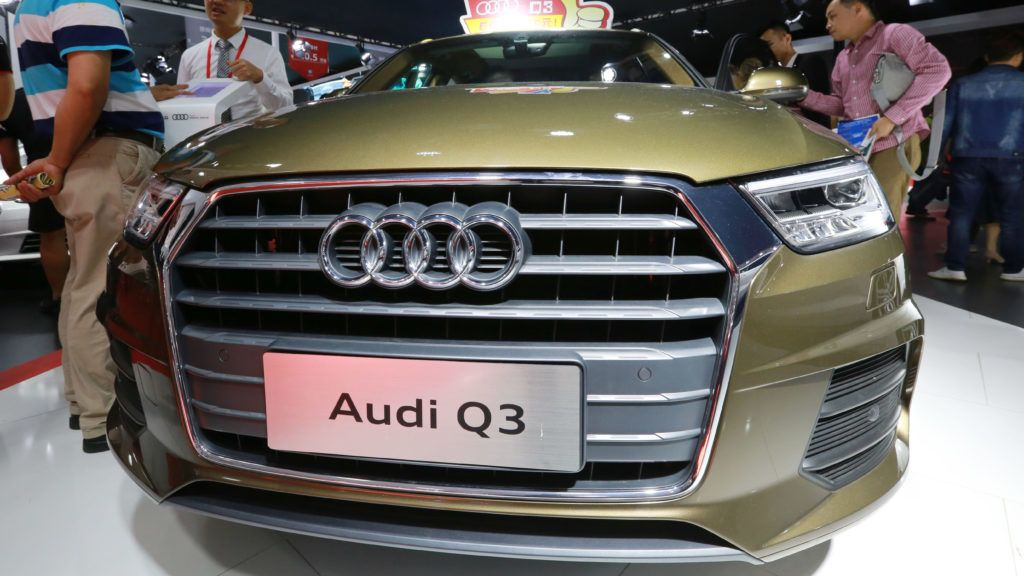 """--FILE--Visitors look at an Audi Q3 during an auto show in Haikou city, south China's Hainan province, 24 March 2018.  Volkswagen's premium brand Audi aims to double sales in China over the coming six years, sales chief Bram Schot told Automobilwoche. """"In 2023 we want to sell 1.2 million cars in China,"""" the German trade magazine quoted him as saying. Audi sold 597,000 vehicles in China, its biggest single market, last year. The company last year resolved a dispute with dealers in China that could have disrupted the luxury carmaker's business in the world's biggest auto market."""