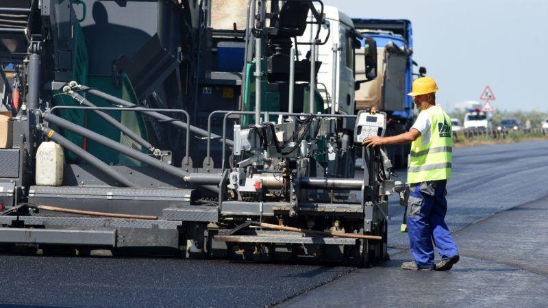 Cegléd, 2018. július 16. Aszfaltburkolatot terítenek le az épülõ M4 gyorsforgalmi út Cegléd és Abony közötti szakaszán, Cegléd közelében 2018. július 16-án. A 17,6 kilométeres szakasz a tervek szerint 2019 negyedik negyedévében készül el. Az út és kapcsolódó létesítményei 26,311 milliárd forint hazai forrásból, a Nemzeti Fejlesztési Minisztérium megbízásából, a NIF Nemzeti Infrastruktúra Fejlesztõ Zrt. beruházásában valósul meg. MTI Fotó: Mészáros János