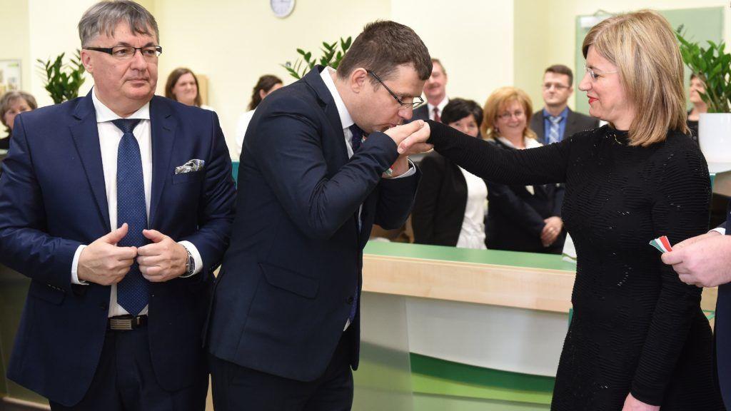 Kisvárda, 2018. március 22. Seszták Miklós nemzeti fejlesztési miniszter kezet csókol Bártfai-Máger Andrea postaügyért és a nemzeti pénzügyi szolgáltatásokért felelõs kormánybiztosnak, balról Leleszi Tibor (Fidesz-KDNP) polgármester, jobbról Illés Zoltán, a Magyar Posta Zrt. elnök-vezérigazgatója a kisvárdai 1-es számú postahivatal Somogyi Rezsõ utcai felújított épületének átadóünnepségén 2018. március 22-én. A 229 millió forintból megújult épület 1914-tõl postaként funkcionál. MTI Fotó: Balázs Attila