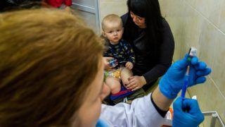 Ungvár, 2018. február 1. Kisgyermek édesanyja ölében ülve várja, hogy kanyaró elleni védõoltást kapjon az egyik háziorvosi rendelõben a kárpátaljai Ungváron 2018. február 1-jén. Január végén nyolcezer adag, a veszélyes, fertõzõ betegség elleni oltóanyagot adott át a magyar kormány humanitárius gyorssegélyként több mint 100 millió forint értékben Grezsa István, Kárpátaljáért felelõs kormánybiztos Ungváron az Ukrán Vöröskereszt Kárpátalja megyei szervezetének. MTI Fotó: Nemes János