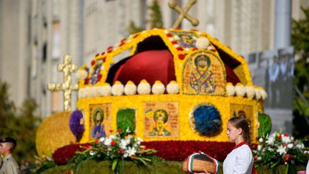 Debrecen, 2018. augusztus 20. Új kenyeret tart a kezében egy lány a Szent Korona virágkocsi mellett a 49. Debreceni Virágkarneválon 2018. augusztus 20-án. MTI Fotó: Czeglédi Zsolt