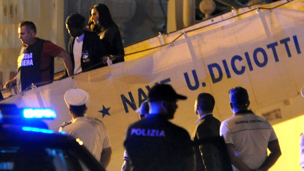 """A migrant disembarks escorted by police from Italy's Diciotti coast guard vessel carrying 67 asylum seekers berthed at Trapani port on July 12, 2018.  The migrants were rescued off Libya on July 10 by a private Italian vessel oil-rig tug Vos Thalassa and then transferred to the coast guard ship in a case that has caused tension within the government. Italy's Interior Minister and deputy PM says on July 12, from migrants summit in Innsbruck """"I do not authorize anyone to get off"""". / AFP PHOTO / Alessandro FUCARINI"""