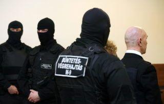 Budapest, 2010. február 23. A büntetés-végrehajtás kommandósai állnak a Fõvárosi Bíróság tárgyalótermében a golyóálló mellényt viselõ Jozef Rohác (j) mellett, aki a vád szerint 1997-ben ismeretlen társaival megkísérelte felrobbantani Seres Zoltán vállalkozót. A Fõvárosi Fõügyészség elõre kitervelten elkövetett emberölés kísérletével és robbanóanyaggal vagy robbantószerrel való visszaéléssel vádolja Rohácot, aki tagadta bûnösségét, de vallomást nem kívánt tenni. MTI Fotó: Mohai Balázs