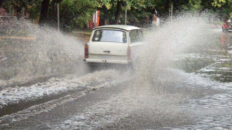 Csongrád, 2011. július 2. Az úttesten felgyülemlett vízen keresztül halad egy autó Csongrádon, ahol jégesõvel kísért felhõszakadás volt a délelõtt folyamán négy alkalommal. A hatalmas mennyiségû lezúdult vizet a csatornák már sok helyen nem tudták elnyelni. A tûzoltókat fõleg az alsóvárosba riasztották vízszivattyúzásokhoz, ahol a házak szobáiba is befolyt a víz. MTI Fotó: Donka Ferenc