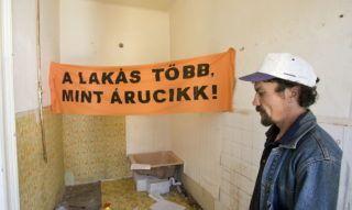 """Budapest, 2010. május 13. A Város Mindenkié csoport aktivistája áll egy """"A lakás több mint árucikk"""" feliratú transzparens mellett egy a IX. kerületi Koppány utcában található épület egyik lakásában, ahol a szervezet aktivistái élõlánccal tiltakoztak egy ferencvárosi család elhelyezés nélküli kilakoltatása ellen. MTI Fotó: Szigetváry Zsolt"""