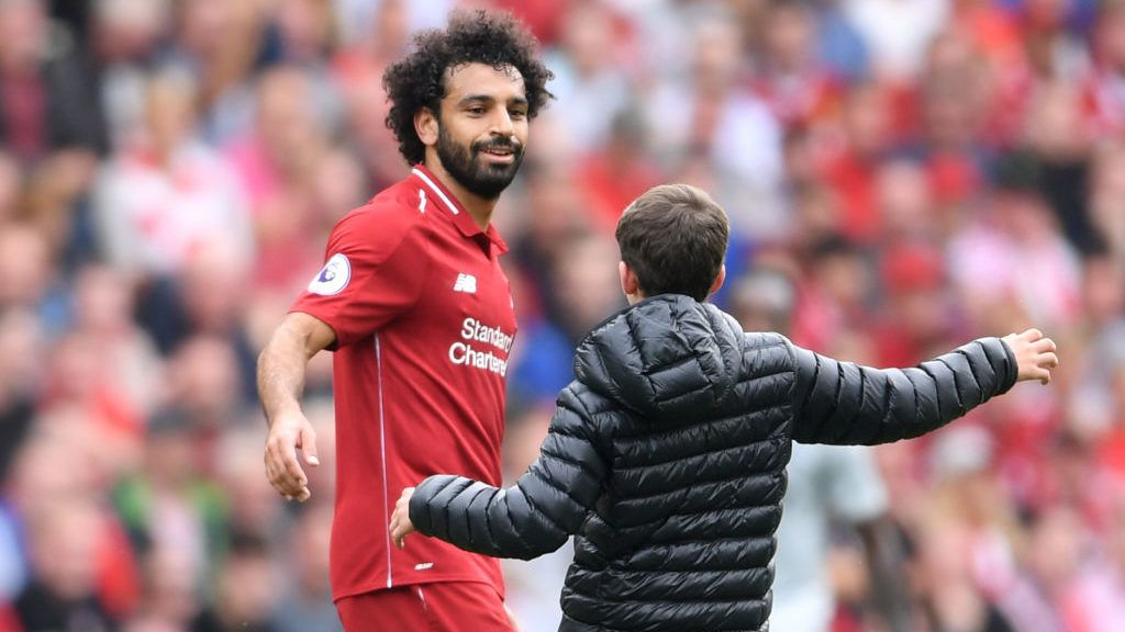 LIVERPOOL, ENGLAND - AUGUST 12:  A fan runs onto the pitch and embraces Mohamed Salah of Liverpool during the Premier League match between Liverpool FC and West Ham United at Anfield on August 12, 2018 in Liverpool, United Kingdom.  (Photo by Laurence Griffiths/Getty Images)