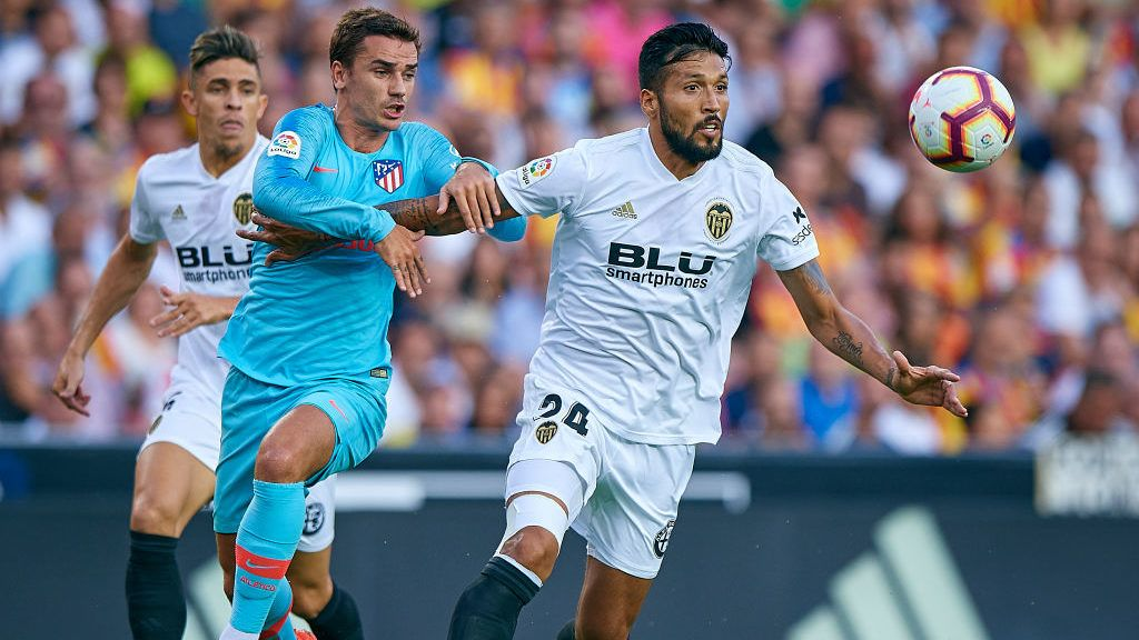 VALENCIA, SPAIN - AUGUST 20:  Ezequiel Garay (R) of Valencia competes for the ball with Antoine Griezmann of Atletico de Madrid during the La Liga match between Valencia CF and Club Atletico de Madrid at Estadio Mestalla on August 20, 2018 in Valencia, Spain.  (Photo by Quality Sport Images/Getty Images)