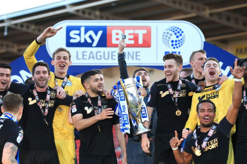 DONCASTER, ENGLAND - MAY 05:  Wigan Athletic lift the trophy as they celebrate becoming League 1 Champions during the Sky Bet League One match between Doncaster Rovers and Wigan Athletic at Keepmoat Stadium on May 5, 2018 in Doncaster, England.  (Photo by Stephen Pond/Getty Images)