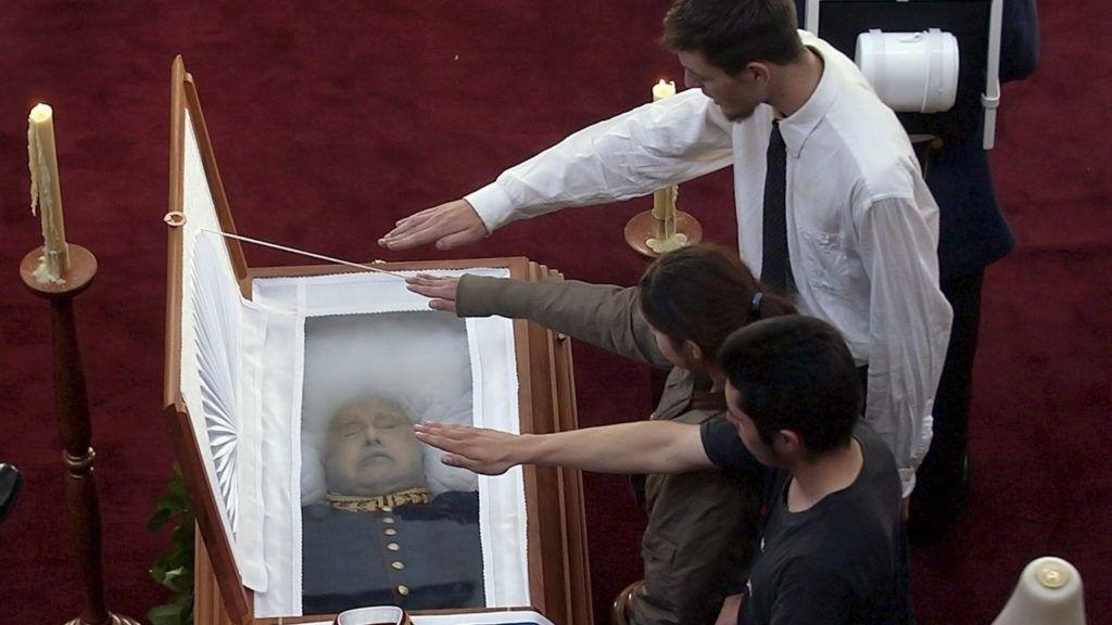 Santiago de Chile, 2006. december 11. Három fiatal fasiszta tisztelgéssel áll az elõtt az üvegezett koporsó elõtt, amelyben Augusto Pinochet tábornok, egykori chilei diktátor holtteste fekszik 2006. december 11-én a santiagói katonai iskolában. Az országot 17 éven át uraló Pinochet elõzõ nap halt meg 91 éves korában szívelégtelenség következtében, egy héttel szívinfarktusa után.  (MTI/EPA/IAN SALAS)