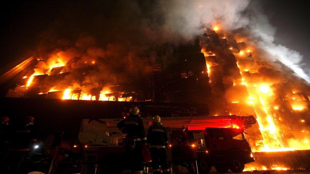 Peking, 2009. február 9. Tûzoltók nézik, amint a befejezetlen, 44 emeletes Mandarin Oriental szállóból hatalmas lángok törnek elõ Pekingben 2009. február 9-én. (MTI/EPA/OLIVER WEIKEN)