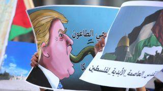 """Ammán, 2017. december 7. Palesztin szimpatizánsok Donald Trump amerikai elnök gúnyrajzával tüntetnek a jordániai fõváros, Ammán amerikai nagykövetsége elõtt 2017. december 7-én. Az elõzõ napon Donald Trump amerikai elnök Jeruzsálemet Izrael fõvárosának ismerte el, és kijelentette, hogy az amerikai nagykövetséget Tel-Avivból Jeruzsálembe költözteti.  Az arab feliratok jelentése: """"Jeruzsálem Palesztina örök fõvárosa"""" és """"Amerika bajkeverõ."""" (MTI/EPA/Mohamed Szaber)"""