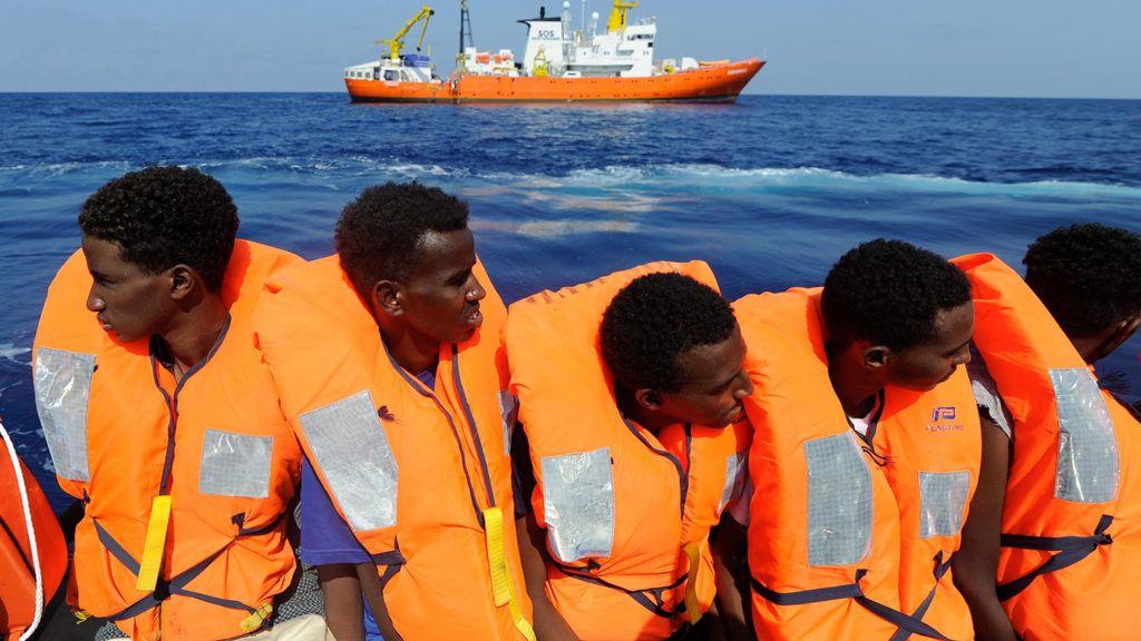 Földközi-tenger, 2018. augusztus 13.Az SOS Méditerranée civil szervezet 2018. augusztus 13-án közreadott felvételén bárkáról felvett, Európába igyekvő afrikai bevándorlókat szállítanak gumicsónakban a szervezet Aquarius mentőhajóra a Földközi-tengeren augusztus 10-én. Az Aquarius európai kikötőt keres 141 migránssal a fedélzetén. (MTI/EPA/SOS Méditerranée/Guglielmo Mangiapane)