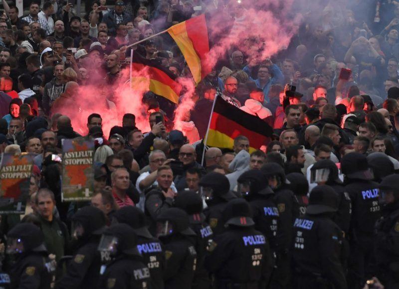 """Chemnitz, 2018. augusztus 27. Szélsõjobboldali tüntetõk és rendõrök a kelet-németországi Chemnitzben két nappal ezelõtt történt gyilkosság miatti tiltakozáson 2018. augusztus 27-én. A chemnitzi rendõrség és az ügyészség korábban arról tájékoztatott, hogy a belvárosban tartott szabadtéri fesztivál szombati programjai után, éjjel összetûzésbe keveredett egy csoport """"különbözõ nemzetiségû férfi"""". Egy ember életét vesztette, ketten súlyos sebesüléseket szenvedtek. Az emberöléssel egy 23 éves szíriai és egy 22 éves iraki állampolgárt gyanúsítanak. (MTI/EPA/Filip Singer)"""