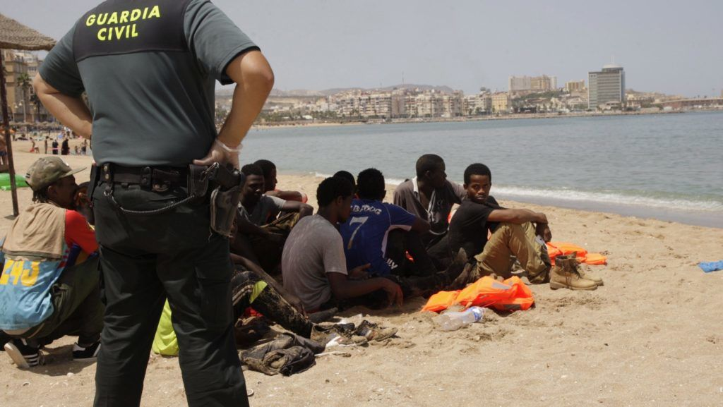Melilla, 2017. augusztus 4. Afrikai migránsokat felügyel egy polgárőr az észak-afrikai Melilla város Hipodromo tengerpartján 2017. augusztus 4-én. Huszonkét illegális bevándorlónak sikerült a spanyol parti őrség figyelmét kijátszva hajóval megközelíteni a Marokkóba ágyazódott spanyol exklávét, ahol a vízi mentők riasztották a polgárőröket. (MTI/EPA/F. G. Guerrero)