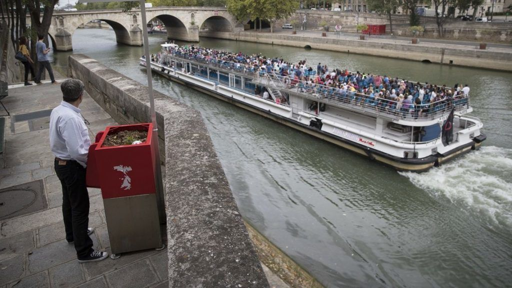 """A man stands at a """"uritrottoir"""" public urinal on August 13, 2018, on the Saint-Louis island in Paris, as a """"bateau mouche"""" tourist barge cruises past. The city of Paris has begun testing """"uritrottoirs"""", dry public urinals intended to be ecological and odorless, but that make some residents cringe. / AFP PHOTO / Thomas SAMSON"""