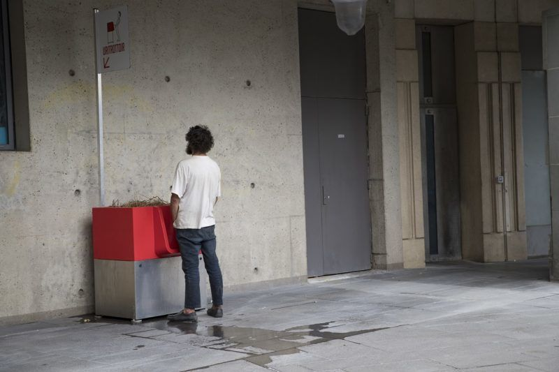 """A man uses a """"uritrottoir"""" public urinal on August 13, 2018, near the Gare de Lyon in Paris. The city of Paris has begun testing """"uritrottoirs"""", dry public urinals intended to be ecological and odorless, but that make some residents cringe. / AFP PHOTO / Thomas SAMSON"""