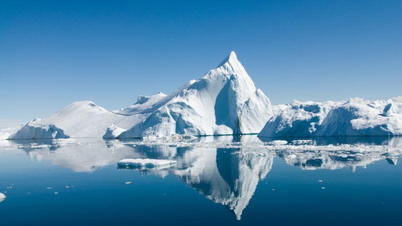 Icebergs drift in calm seas off the Greenland coast.