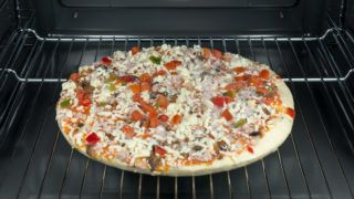 Raw and frozen pizza in the oven.