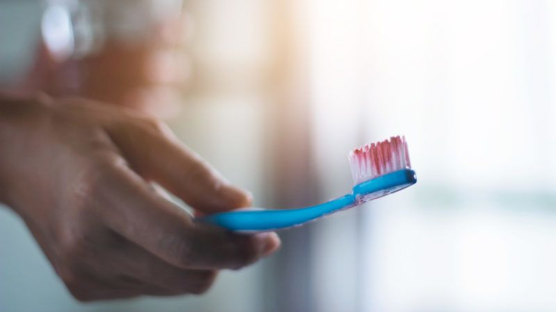 Toothbrush with scurvy in a bubble toothpaste on the bathroom background