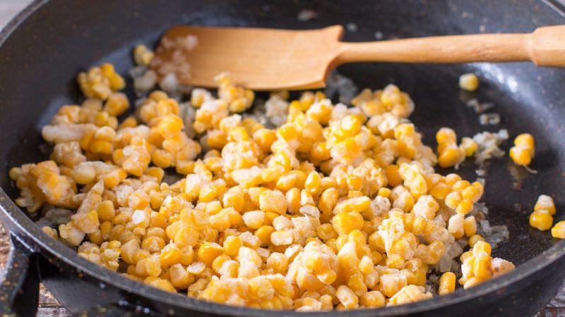 Frozen sweet corn in a frying pan on table