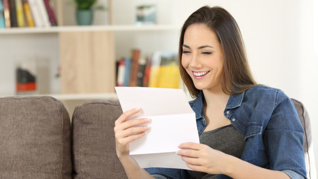 Happy woman reading a letter sitting on a couch in the living room at home