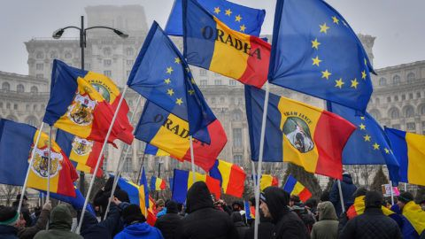 Demonstrators hold flags of Europe and of Romania as they protest in the front of the Romanian Parliament in Bucharest March 6, 2018.Hundreds of demonstrators from around the country staged a rally following a nation wide mobilisation on social media to protest against the corruption and against PSD, the ruling Social Democrat Party. Romania's justice minister launched a procedure to sack the popular and internationally respected head of the anti-corruption investigation body. As chief prosecutor in the DNA anti-corruption body, Laura Codruta Kovesi has helped bring a raft of corrupt officials to justice in recent years in one of the EU's most graft-ridden countries. / AFP PHOTO / Daniel MIHAILESCU