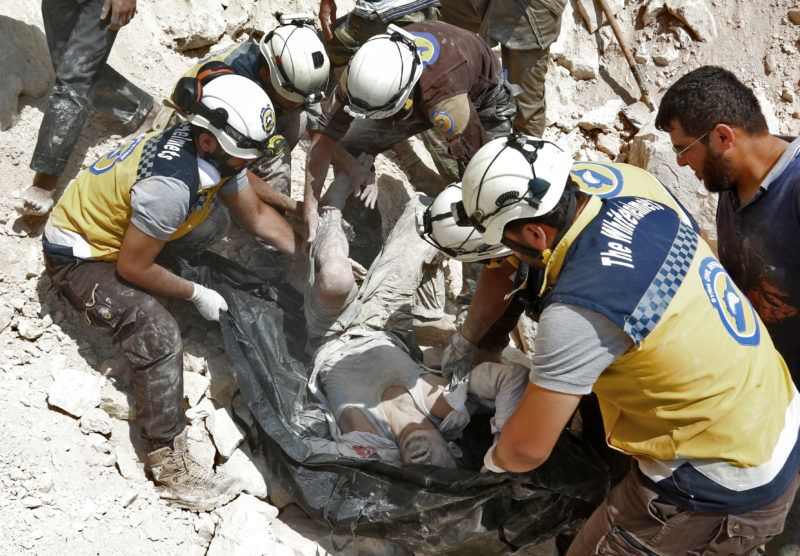"""This picture taken in Kafr Ain on September 7, 2018, shows members of the Syrian Civil Defence, also known as the """"White Helmets"""", carrying a victim after airstrikes, four kilometers east of Khan Shaykhun in the southern countryside of Idlib province. / AFP PHOTO / Anas AL-DYAB"""