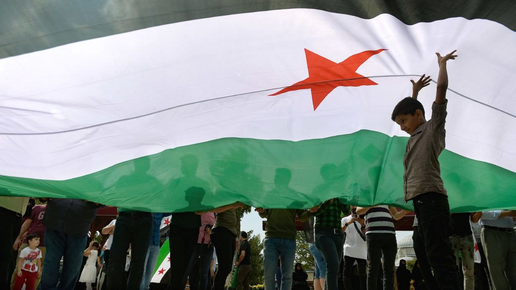 A child stands under a Free Syrian Army (FSA) flag during a protest against a Syrian military operation in the rebel-held Idlib province of northwest Syria in front of the Fatih mosque in Istanbul on September 7, 2018.  / AFP PHOTO / Yasin AKGUL