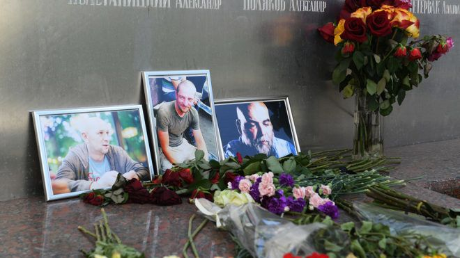 5603647 03.08.2018 Flowers at the photos of the three Russian journalists killed in the Central African Republic, from right: Orkhan Dzhemal, Kirill Radchenko and Alexander Rastorguyev, outside the Central House of Journalists in Moscow. Ekaterina Chesnokova / Sputnik