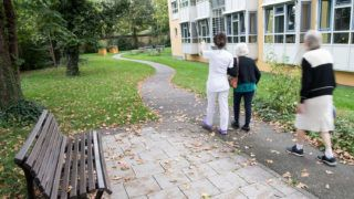 """13 September 2018, Bavaria, Munich: 13 September 2018, Germany, Munich: A nurse walks with two ladies in need of care through the garden of the protective area of Muenchenstift GmbH. (to dpa """"""""As much freedom as possible"""" - Architecture for dementia patients"""" of 14.09.2018) Photo: Peter Kneffel/dpa"""