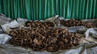 """A picture taken on April 30, 2018, shows collected victims' bones and skulls from a newly discovered pit which was used as mass grave during 1994 Rwandan genocide and hidden under a house at the local administration office in Kabuga, the outskirts of Kigali, Rwanda. According to the main association of the genocide survivors IBUKA, the word for """"remember"""" in Kinyarwanda, four pits have discovered at the local resident's house by survivor's information at the begging of April, 2018. By the numbers of thighbone, 207 bodies have been found from the first pit which reaches about 25 meters deep. Around 800,000 people were slaughtered in Rwanda between April and July 1994 at the instigation of the hardline Hutu government. / AFP PHOTO / Yasuyoshi CHIBA"""
