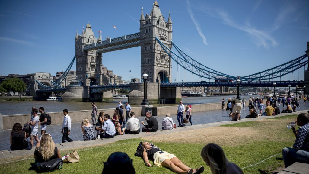 A woman takes a nap in the sunshine at Potters Fields Park near Tower Bridge in central London on July 2, 2018, as the country basks in a hot summer spell. / AFP PHOTO / Tolga AKMEN