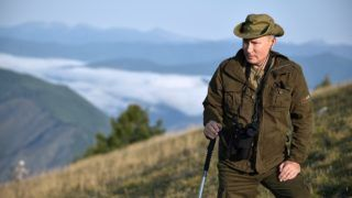 A picture taken on August 26, 2018, shows Russian President Vladimir Putin standing on a mountain during a short vacation in the remote Tuva region in southern Siberia. / AFP PHOTO / Sputnik / Alexey NIKOLSKY