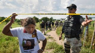 A relative of a missing person enters on September 17, 2018, the site where a mass grave was found in El Arbolillo, Alvarado municipality, in the Mexican southeastern state of Veracruz, a region hit by bloody drug cartel turf wars. At least 174 bodies alongside personal belongings were found in 33 mass graves at El Arbolillo's narco-cemetery.  / AFP PHOTO / VICTORIA RAZO