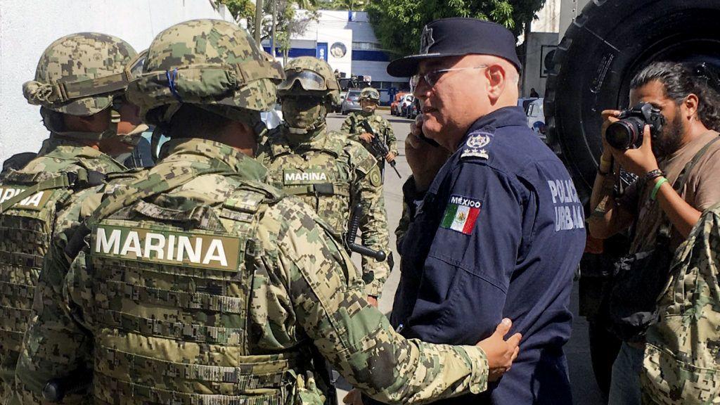 Mexican Navy members escort the Secretary of Public Security of Acapulco Max Lorenzo Sedano (R) after they took control of the local Public Security Secretariat in Acapulco, state of Guerrero, Mexico, on September 25, 2018.  Mexican military forces arrested three police officers of the Mexican resort of Acapulco and took control of the local Public Security Secretariat due to possible leaks of organized crime in the institution, authorities confirmed / AFP PHOTO / FRANCISCO ROBLES