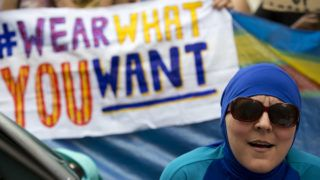 """A woman wearing a """"Burkini"""" joins a protest outside the French Embassy in London on August 25, 2016, during a """"Wear what you want beach party"""" to demonstrate against the ban on Burkinis on French beaches and to show solidarity with Muslim women. French Interior Minister Bernard Cazeneuve warned Wednesday against stigmatising Muslims, as a furore over the banning of burkinis grew with the emergence of pictures showing police surrounding a veiled woman on a beach.  Dozens of French towns and villages, mostly on the Cote d'Azur, have banned beachwear that """"conspicuously"""" shows a person's religion -- a measure aimed at the full-body Islamic swimsuit but which has also been used against women wearing long clothes and a headscarf. / AFP PHOTO / JUSTIN TALLIS"""