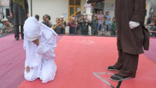 An Acehnese woman gets caned by a religious officer, for spending time in close proximity with a man who is not her husband, which is against Sharia law, in Banda Aceh on February 27, 2017.   Aceh is the only province in the world's most populous Muslim-majority country that imposes sharia law. People can face floggings for a range of offences -- from gambling, to drinking alcohol, to gay sex. / AFP PHOTO / CHAIDEER MAHYUDDIN