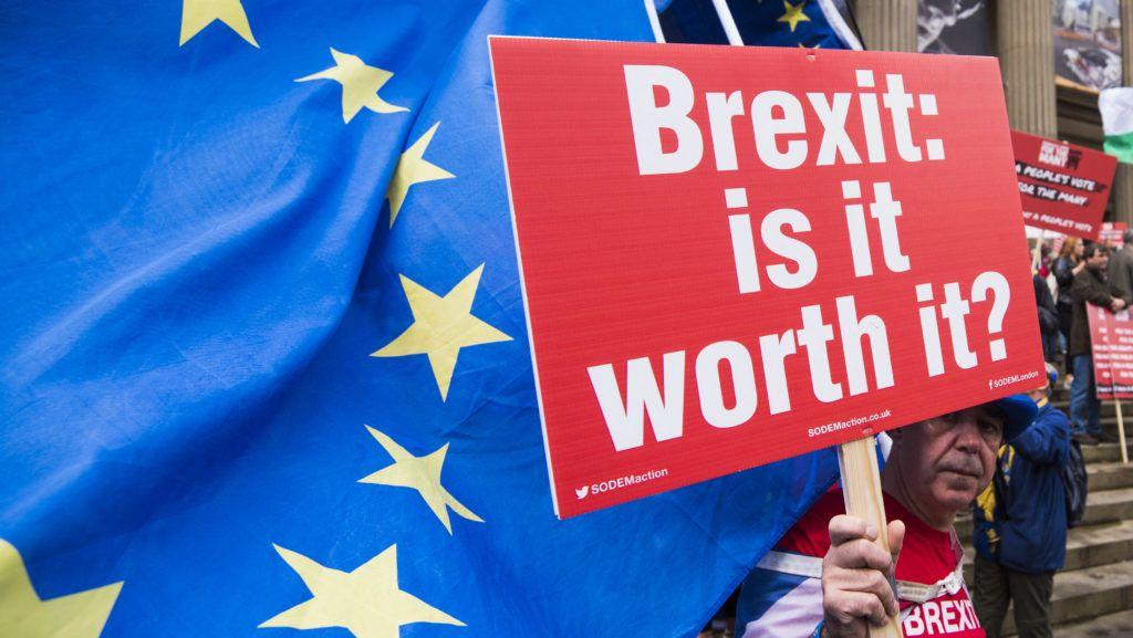 """An anti-Brexit protester holds a """"Brexit, is it worth it?"""" sign at the People's Vote March for the Many in Liverpool, United Kingdom where hundreds rallied to protest against Brexit and ask for a referendum on the final Brexit deal, as the Labour Party conference takes place in Liverpool - September 23, 2018.  Un manifestant anti-Brexit porte une pancarte sur laquelle est écrit '""""Brexit, en vaut-il le coup ?"""" lors de la marche du """"People's Vote March for the Many"""" à Liverpool au Royaume-Uni où des centaines de personnes se sont rassemblés pour demander un referendum sur l'accord final de la sortie du Royaume-Uni de l'Union européenne, alors que le sommet annuel du parti travailliste britannique se tient dans à Liverpool - 23 Septembre 2018."""