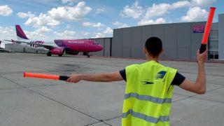 Debrecen, 2017. május 15. A földi személyzet tagja helyére irányítja a Wizzair érkező gépét a Debrecen nemzetközi repülőtéren, melynek megnyitásának első hét évében megtízszereződött a forgalma. Az aktív turizmus idején, május és szeptember között további 15 százalékos utasforgalom növekedés várható. MTVA/Bizományosi: Oláh Tibor ***************************Kedves Felhasználó!Ez a fotó nem a Duna Médiaszolgáltató Zrt./MTI által készített és kiadott fényképfelvétel, így harmadik személy által támasztott bárminemű – különösen szerzői jogi, szomszédos jogi és személyiségi jogi – igényért a fotó készítője közvetlenül maga áll helyt, az MTVA felelőssége e körben kizárt.